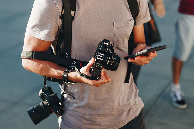 latest photography trends in 2019, male photographer looking at phone